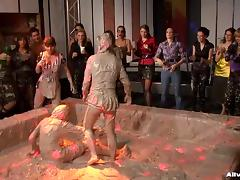 Angry girls wage war in a muddy pool fiercely with a large crowd cheering