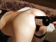 Giant wine bottle stuffed in her gaping asshole